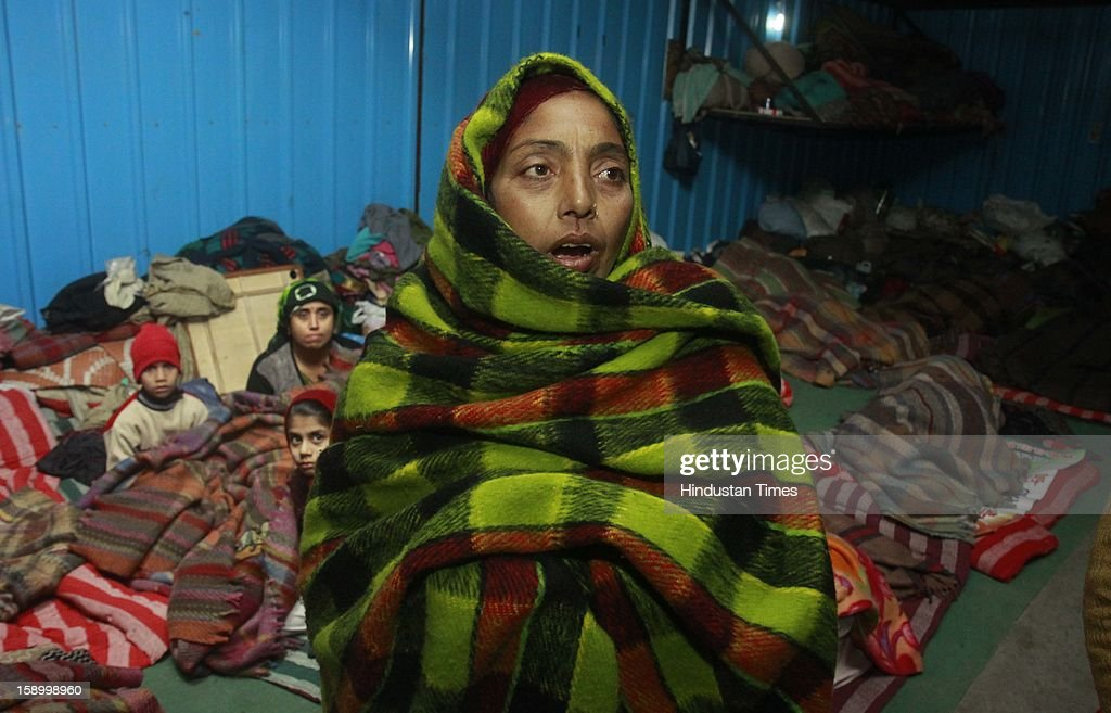 Labor worker and homeless Woman, Sita Devi wrapped in a quilt, sits in cold winter night at Baba Khadak Singh Marg on January 4, 2013 in New Delhi, India. Delhi continued to shiver at a minimum of 2.9 degrees, four notches below normal. Over a 175 people have died so far in the bitter cold in Northern India.