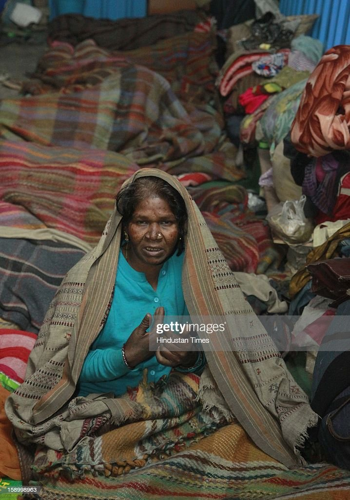 Labor worker and homeless Women;s , Phul wati wrapped in a quilt, sits in cold winter night at Baba Khadak Singh Marg on January 4, 2013 in New Delhi, India. Delhi continued to shiver at a minimum of 2.9 degrees, four notches below normal. Over a 175 people have died so far in the bitter cold in Northern India.