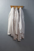 Laboratory coat hanging on hook against wall