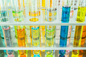 Laboratory glass test tubes with colorful chemical solution in test tubes rack, science background