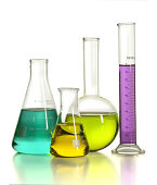Laboratory glassware with colored liquids over reflective table over white background
