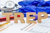TREP laboratory medical abbreviation treponemal antibodies (syphilis) concept photo. On table is laboratory acronym TREP next to tubes of blood, other biological fluids, result analysis, stethoscope