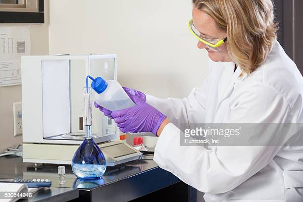 Laboratory scientist adding distilled water to water sample flask