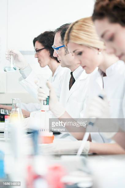 Laboratory technician at work, other scientist on background