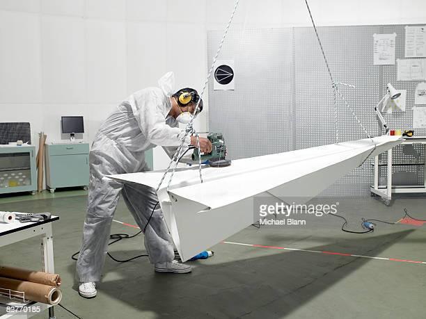 laboratory technician sanding paper plane