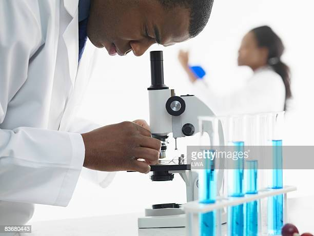 Laboratory technician using microscope