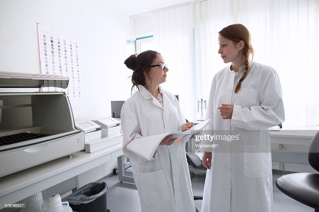 Laboratory technicians in laboratory with journal