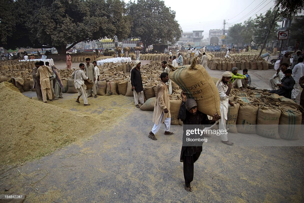 A laborer carries a bag of rice at a rice market in the Chiniot district of Punjab province, Pakistan, on Saturday, Oct. 13, 2012. Rice exports from Pakistan, the fourth-largest shipper, are set to rebound from November with the new harvest after a rally in domestic prices and cheaper supplies from India cut shipments, a traders' group said. Photographer: Asad Zaidi/Bloomberg via Getty Images
