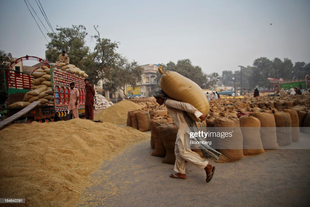 A laborer carries a bag of rice to a truck at a rice market in the Chiniot district of Punjab province, Pakistan, on Saturday, Oct. 13, 2012. Rice exports from Pakistan, the fourth-largest shipper, are set to rebound from November with the new harvest after a rally in domestic prices and cheaper supplies from India cut shipments, a traders' group said. Photographer: Asad Zaidi/Bloomberg via Getty Images