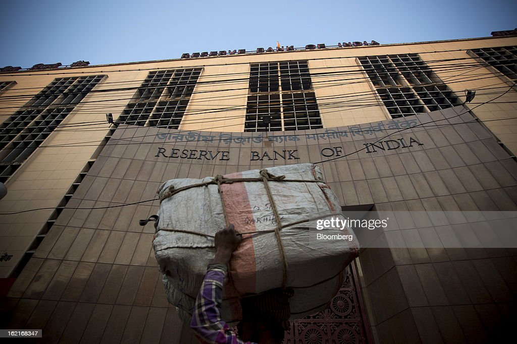 A laborer carries a parcel past the Reserve Bank of India (RBI) in the BBD Bagh area of Kolkata, India, on Tuesday, Feb. 19, 2013. India's slowest economic expansion in a decade is limiting profit growth at the biggest companies even as foreigners remain net buyers of the nation's stocks, according to Kotak Institutional Equities. Photographer: Brent Lewin/Bloomberg via Getty Images