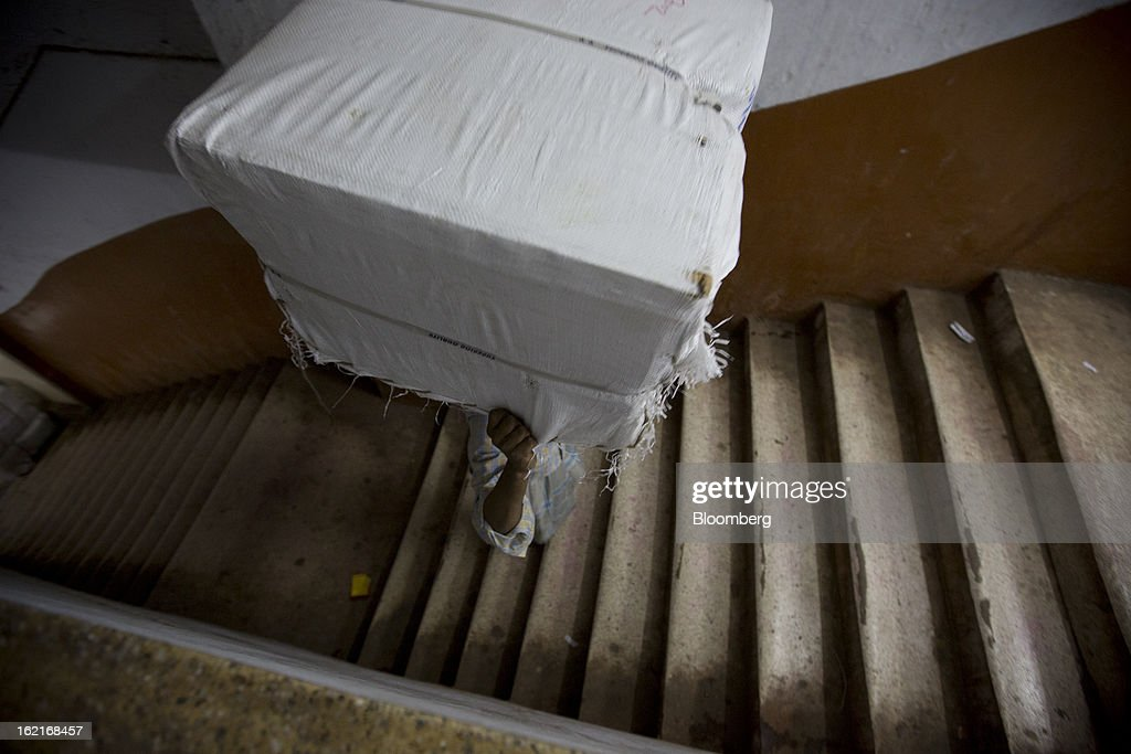 A laborer carries goods up stairs in a building in the Burrabazar area of Kolkata, India, on Tuesday, Feb. 19, 2013. India's slowest economic expansion in a decade is limiting profit growth at the biggest companies even as foreigners remain net buyers of the nation's stocks, according to Kotak Institutional Equities. Photographer: Brent Lewin/Bloomberg via Getty Images