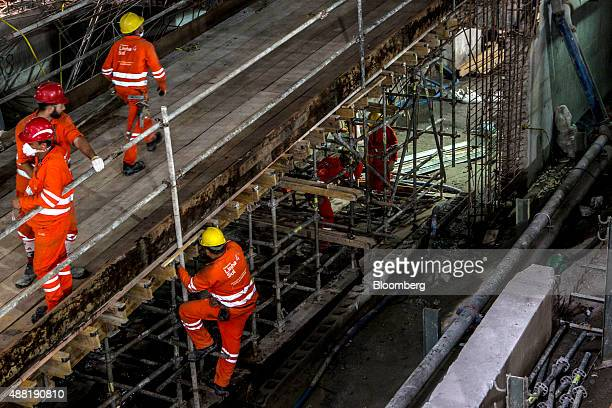 A laborer climbs scaffolding during construction at the Nossa Senhora da Paz metro station on the 4 Line of the subway system in Rio de Janeiro...