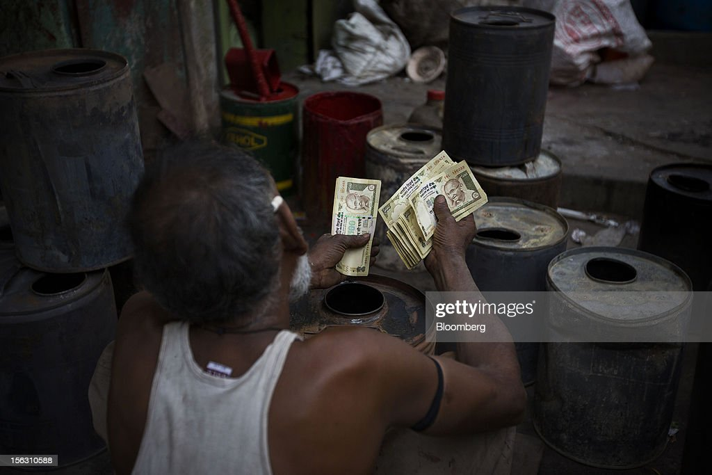 A laborer counts money in the Dharavi slum area of Mumbai, India, on Friday, Nov. 9, 2012. Indian industrial production unexpectedly fell in September and the trade deficit widened to a record last month as exports declined, adding to signs that Asia's third-largest economy is struggling. Photographer: Brent Lewin/Bloomberg via Getty Images