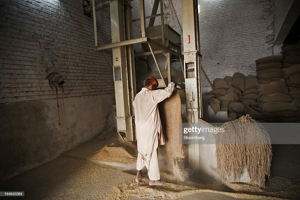 A laborer empties a bag of rice in a rice-processing factory in the Chiniot district of Punjab province, Pakistan, on Saturday, Oct. 13, 2012. Rice exports from Pakistan, the fourth-largest shipper, are set to rebound from November with the new harvest after a rally in domestic prices and cheaper supplies from India cut shipments, a traders' group said. Photographer: Asad Zaidi/Bloomberg via Getty Images