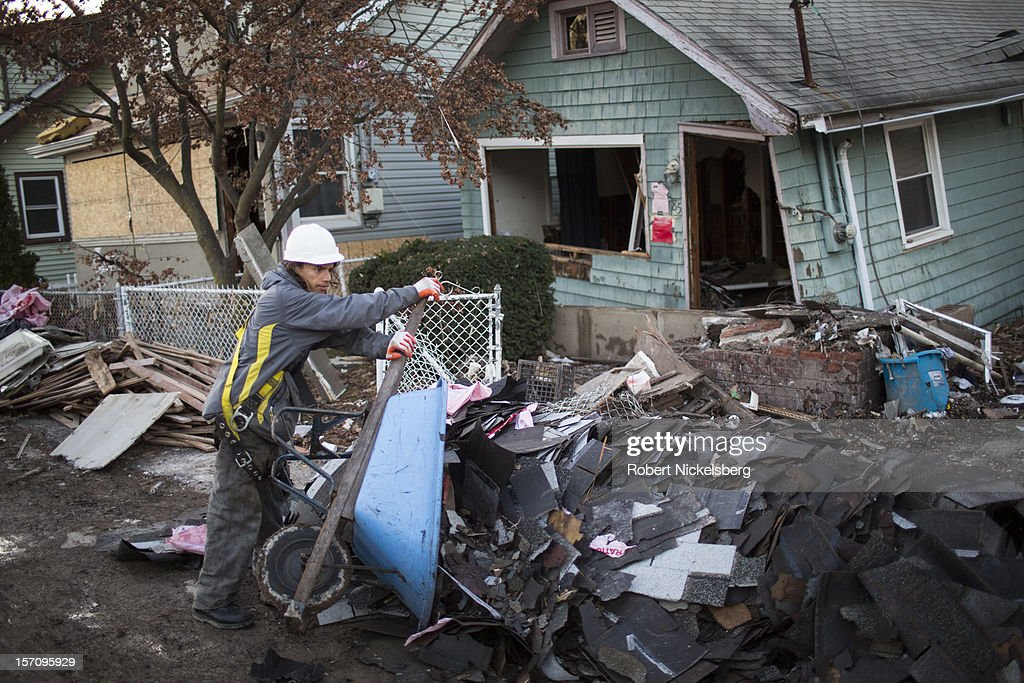 A laborer empties a wheelbarrow of shingles n front of a destroyed home November 28, 2012 in New Dorp Beach in the Staten Island borough of New York City. Parts of the New Dorp Beach neighborhood were submerged under 10 feet of water during the height of Superstorm Sandy one month ago.