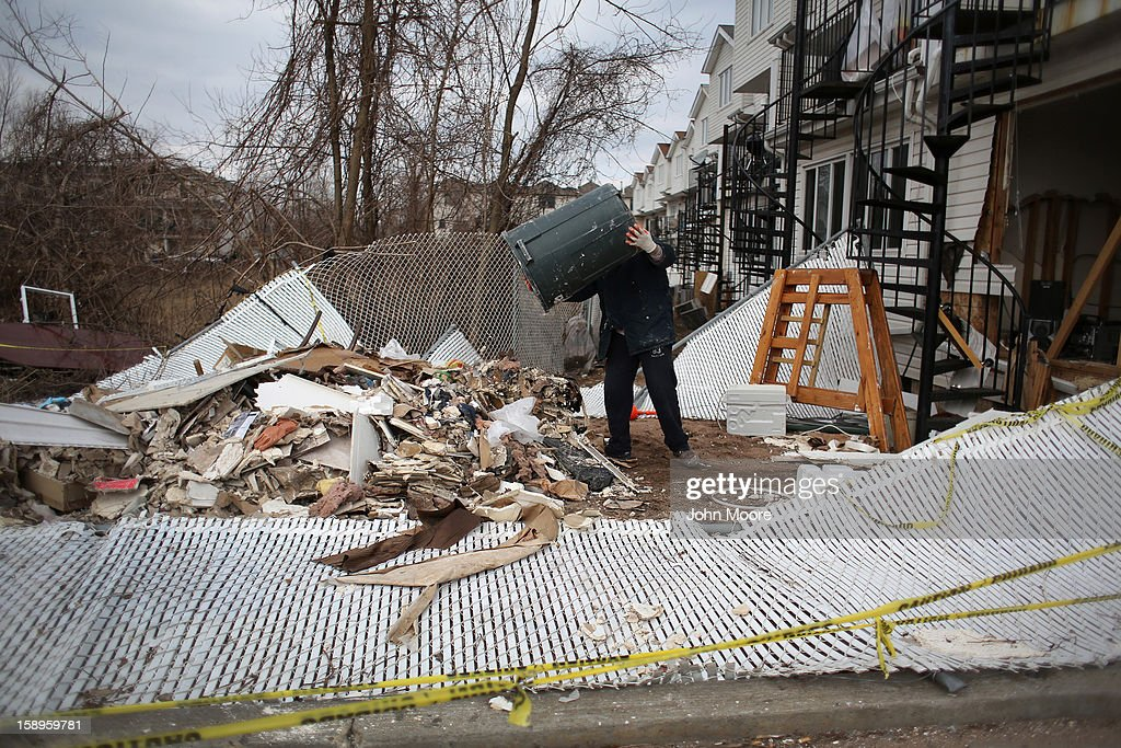 A laborer empties debris from a home damaged by Superstorm Sandy on January 4, 2013 in the Midland Beach area of the Staten Island borough of New York City. More than two months after the storm, Congress passed legislation today that will provide $9.7 billion to cover insurance claims filed by people whose homes were damaged or destroyed by Sandy.
