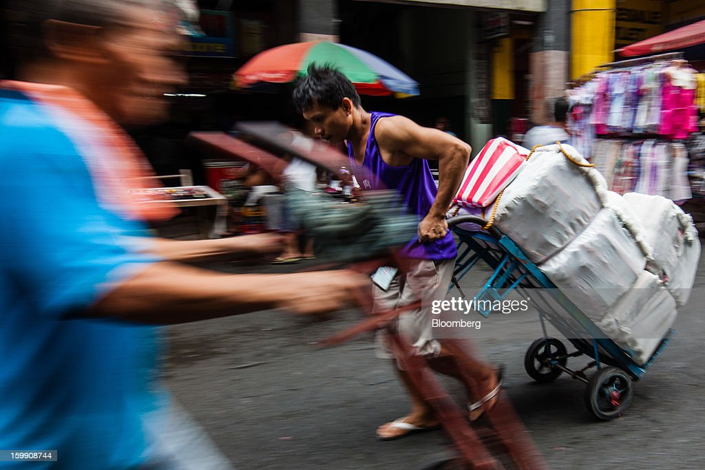 A laborer hauls bags of goods on a cart at the Divisoria market in Manila, the Philippines, on Tuesday, Jan. 22, 2013. Philippine government bonds advanced on speculation the central bank will hold its benchmark interest rate at a record low at a meeting tomorrow, supporting demand for the nation's debt. Photographer: Julian Abram Wainwright/Bloomberg via Getty Images