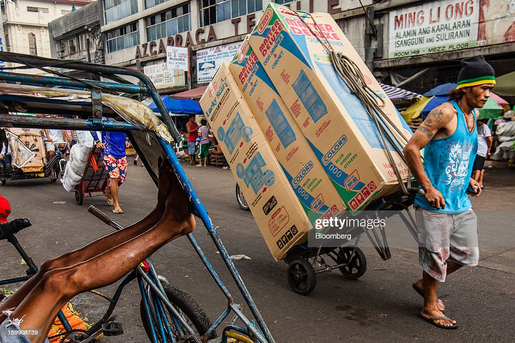 A laborer hauls boxes of goods on a cart as a cycle-rickshaw driver rests at the Divisoria market in Manila, the Philippines, on Tuesday, Jan. 22, 2013. Philippine government bonds advanced on speculation the central bank will hold its benchmark interest rate at a record low at a meeting tomorrow, supporting demand for the nation's debt. Photographer: Julian Abram Wainwright/Bloomberg via Getty Images