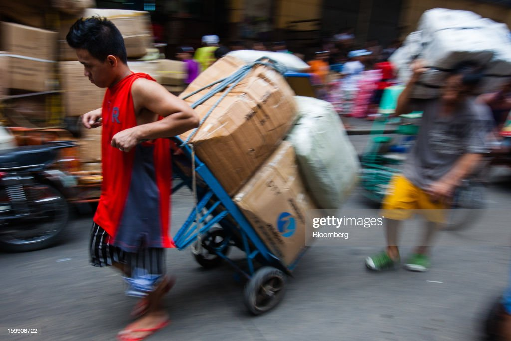 A laborer hauls boxes of goods on a cart at the Divisoria market in Manila, the Philippines, on Tuesday, Jan. 22, 2013. Philippine government bonds advanced on speculation the central bank will hold its benchmark interest rate at a record low at a meeting tomorrow, supporting demand for the nation's debt. Photographer: Julian Abram Wainwright/Bloomberg via Getty Images