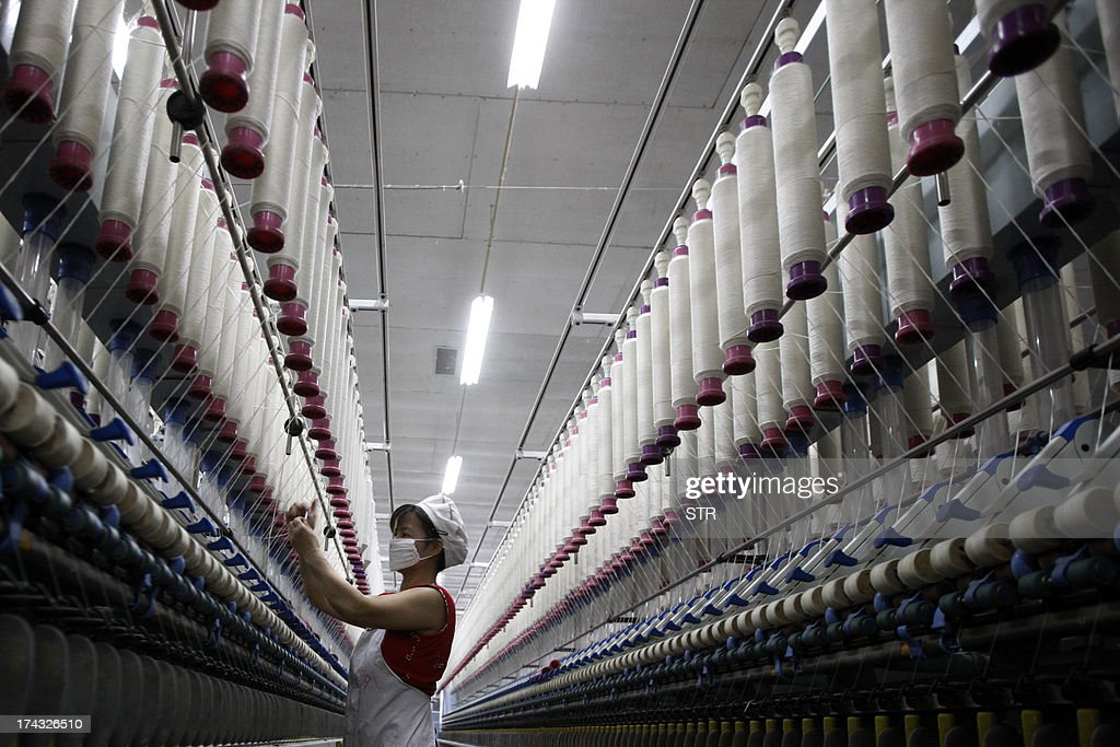 A laborer is seen working in a textile factory in Huaibei, in north China's Anhui province on July 24, 2013. China's manufacturing activity contracted to a 11-month low in July, an HSBC survey showed on July 24, the first evidence of the Asian economic giant losing further momentum in the third quarter. CHINA