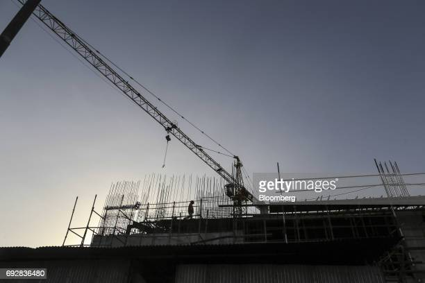 A laborer is silhouetted as he works at a construction site in Palava City on the outskirts of Mumbai India on Thursday May 25 2017 Lodha Group best...