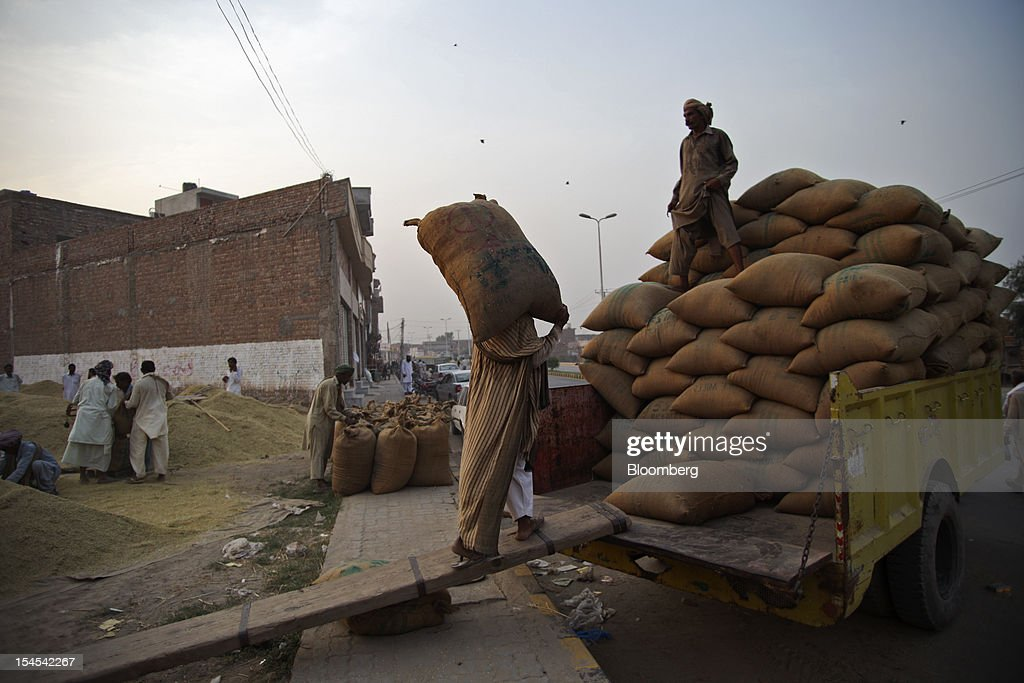 A laborer loads a bag of rice onto a tractor trolley at a rice market in the Chiniot district of Punjab province, Pakistan, on Saturday, Oct. 13, 2012. Rice exports from Pakistan, the fourth-largest shipper, are set to rebound from November with the new harvest after a rally in domestic prices and cheaper supplies from India cut shipments, a traders' group said. Photographer: Asad Zaidi/Bloomberg via Getty Images