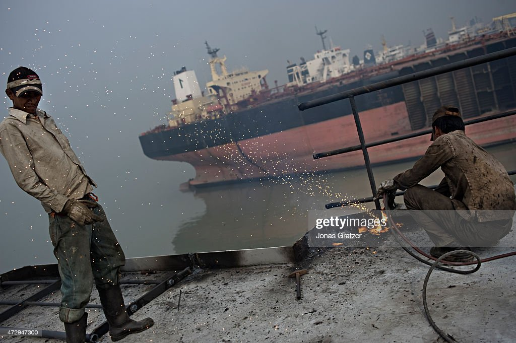 A laborer on top of a mega freighter that has been left on Chittagong beach is cutting through some railing to gather the scrap metal whilst...