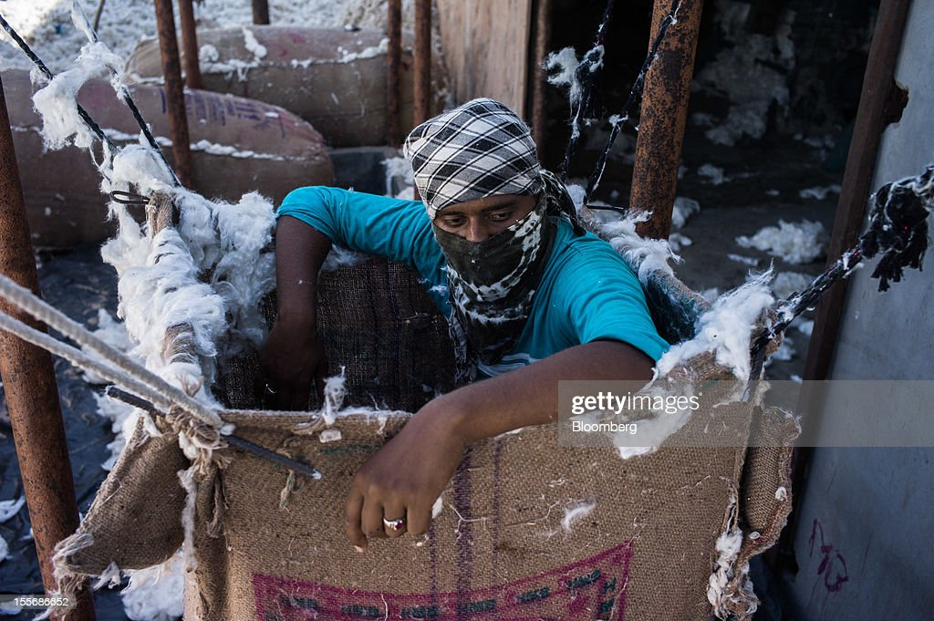 A laborer pauses in between stacking sacks of cotton at a processing plant in Mathania, in the district of Jodhpur in Rajasthan, India, on Monday, Oct. 29, 2012. Cotton shipments from India, the world's second-largest grower, are set to tumble, forcing the government to make record purchases to stem a slide in prices. Photographer: Sanjit Das/Bloomberg via Getty Images