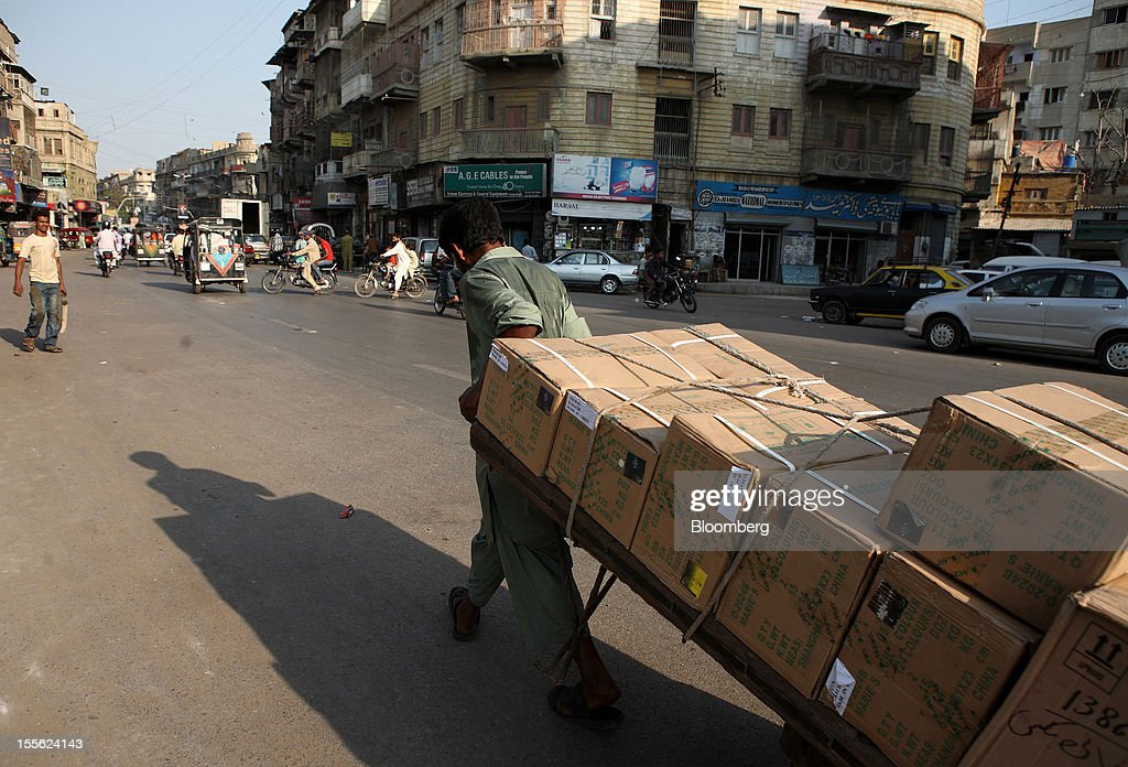 A laborer pulls a cart laden with boxes along M.A. Jinnah Road in Karachi, Pakistan, on Wednesday, Oct. 31, 2012. Businesses in Pakistan's commercial capital are bracing for a surge in extortion demands as parties representing the city's ethnic communities seek to use their hired guns to build financial war chests ahead of parliamentary polls due in the first half of next year. Photographer: Asim Hafeez/Bloomberg via Getty Images