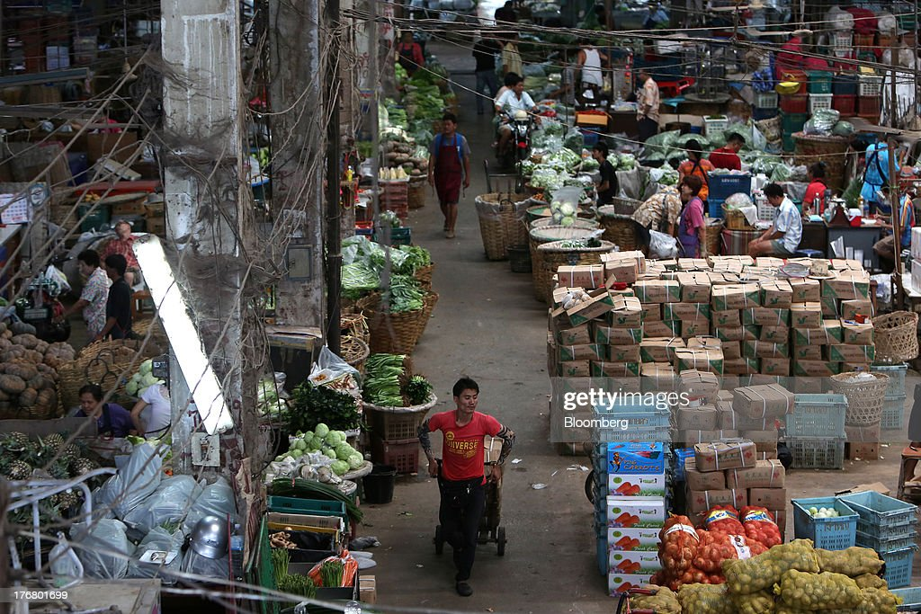 A laborer pulls a cart loaded with goods past fruit and vegetable stalls at the Pak Khlong market in Bangkok, Thailand, on Sunday, Aug. 18, 2013. Thai economic growth slowed for a second quarter as exports cooled and local demand weakened, with rising household debt restricting the scope for monetary easing. Photographer: Dario Pignatelli/Bloomberg via Getty Images