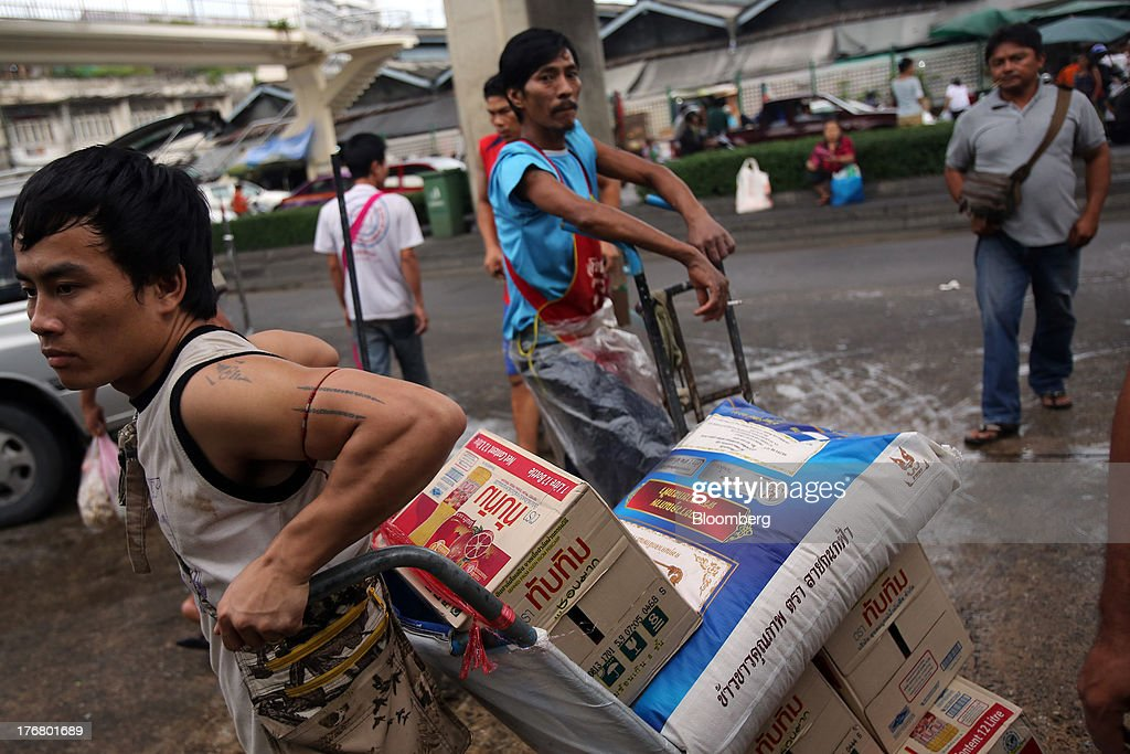 A laborer pulls a cart loaded with rice and other food products at the Klong Thoei market in Bangkok, Thailand, on Sunday, Aug. 18, 2013. Thai economic growth slowed for a second quarter as exports cooled and local demand weakened, with rising household debt restricting the scope for monetary easing. Photographer: Dario Pignatelli/Bloomberg via Getty Images