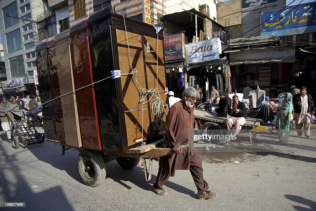 A laborer pulls a handcart loaded with cabinets through a market in Rawalpindi, Pakistan, on Sunday, Dec. 30, 2012. Pakistan's economy will probably expand 3.5 percent in the 12 months through June, the International Monetary Fund forecast Nov. 29, less than the 4.3 percent predicted by the government. Photographer: Asad Zaidi/Bloomberg via Getty Images