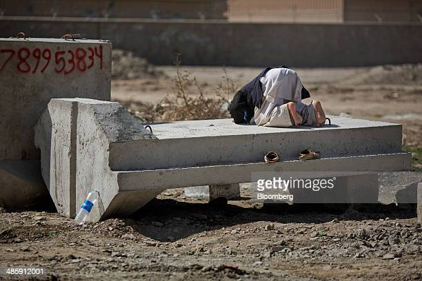 A laborer says his afternoon prayers on top of a concrete blast wall at a facility north of Kabul Afghanistan on Monday April 14 2014 The US and its...