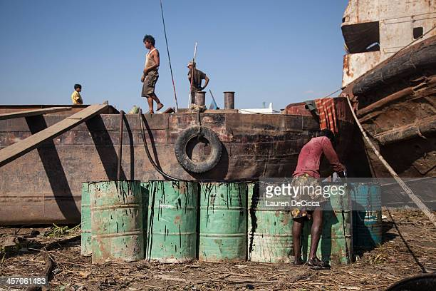 A laborer stacks recycled oil drums weighing 240kg on the banks of the Irrawaddy River in the Dala township of Yangon on December 16 2013 in Yangon...