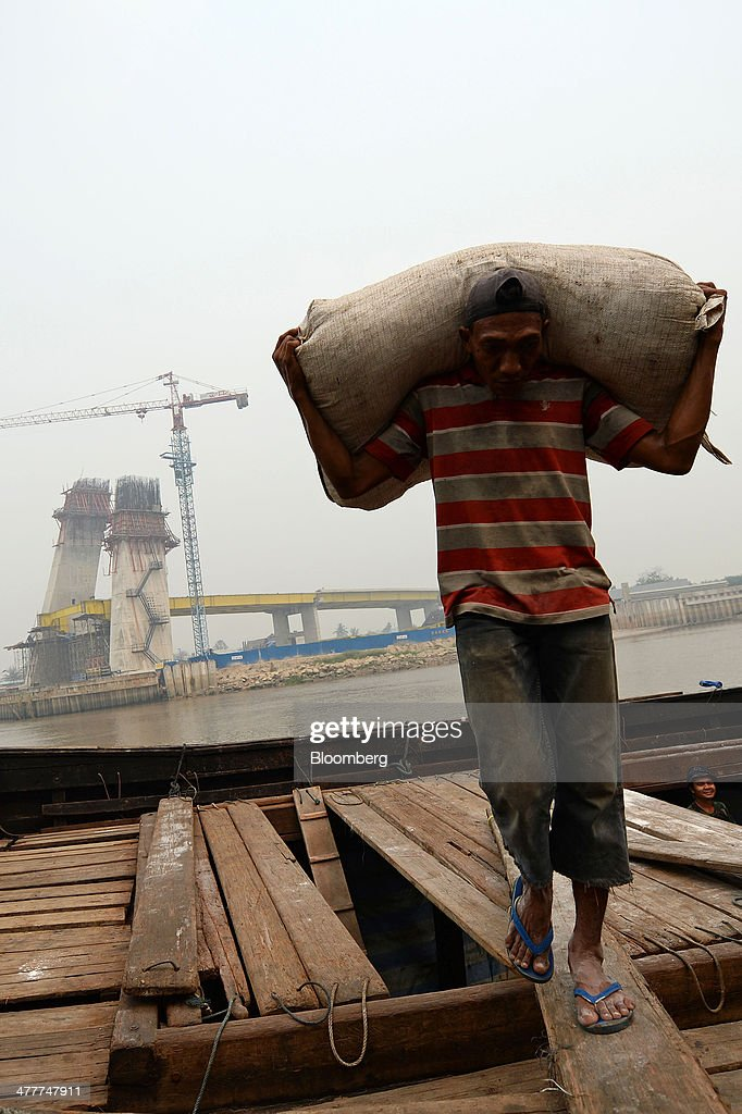A laborer unloads goods from a boat as a new bridge stands under construction across the Siak river in Pekanbaru, Riau Province, Indonesia on Friday, March 7, 2014. Indonesian central bank Governor Agus Martowardojo embarked on the country's most aggressive rate-increase cycle in eight years within a month of taking the helm in May to shore up the rupiah and damp price pressures. Photographer: Dimas Ardian/Bloomberg via Getty Images