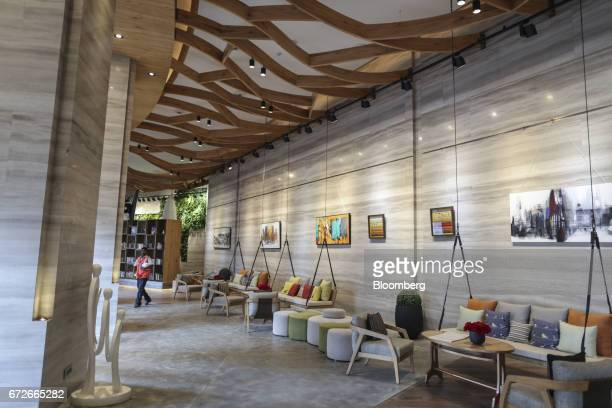 A laborer walks inside the art gallery area of The World Towers a luxury residential project developed by Lodha Developers Ltd in Mumbai India on...