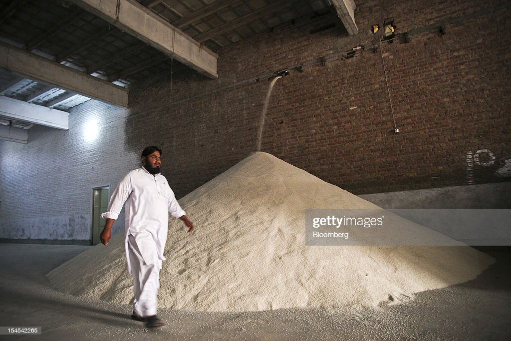 A laborer walks past processed rice in a rice-processing factory in the Chiniot district of Punjab province, Pakistan, on Saturday, Oct. 13, 2012. Rice exports from Pakistan, the fourth-largest shipper, are set to rebound from November with the new harvest after a rally in domestic prices and cheaper supplies from India cut shipments, a traders' group said. Photographer: Asad Zaidi/Bloomberg via Getty Images