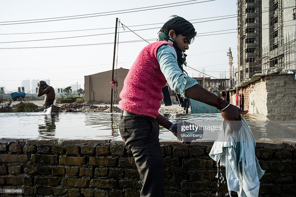 A laborer washes clothes next to a construction site in Noida, Uttar Pradesh, India, on Wednesday, Jan. 9, 2013. India's Finance Ministry predicts GDP growth of as little as 5.7 percent in the year to March 31, the least in a decade. Photographer: Sanjit Das/Bloomberg via Getty Images