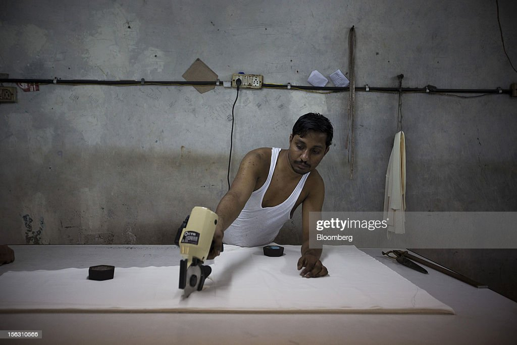 A laborer works at a garment workshop in the Dharavi slum area of Mumbai, India, on Friday, Nov. 9, 2012. Indian industrial production unexpectedly fell in September and the trade deficit widened to a record last month as exports declined, adding to signs that Asia's third-largest economy is struggling. Photographer: Brent Lewin/Bloomberg via Getty Images