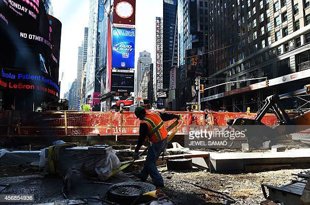 A laborer works on a footpath and road way construction site in Times Square on October 8 2014 in New York The September US employment report showed...