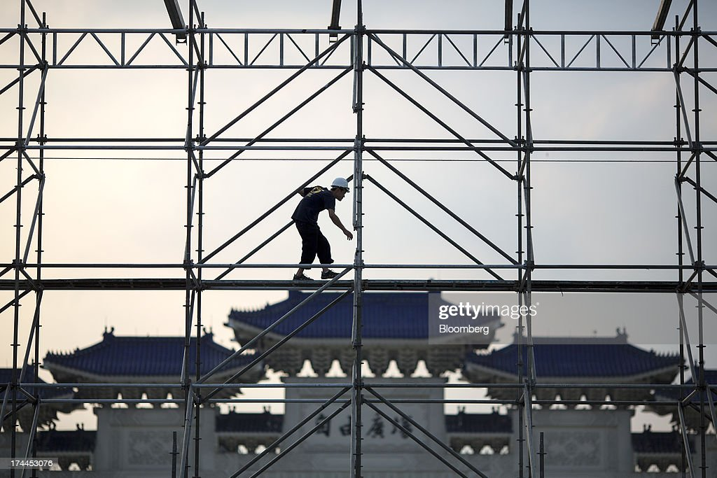 A laborer works on scaffolding for an upcoming event at the Chiang Kai Shek Memorial Hall plaza in Taipei, Taiwan, on Wednesday, July 24, 2013. Taiwan President Ma Ying-jeou ruled out driving down the Taiwan dollar to boost exports following the currencys rally against the yen and said the government still aims for growth of at least 2 percent this year. Photographer: Jerome Favre/Bloomberg via Getty Images