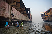 Laborers are walking on the muddy beach of Chittagong where mega freighters have been left for disassembling by poor workers Where do the mega...