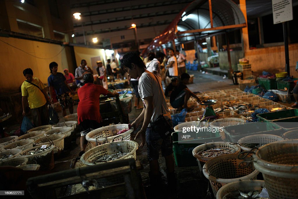 Laborers arrange baskets full of different kinds of fish for customers at the Sandakan central fish market in the Malaysian Borneo state of Sabah on February 4, 2013. Sandakan is the second-largest city in Sabah, eastern Malaysia, on the northeastern coast of Borneo.