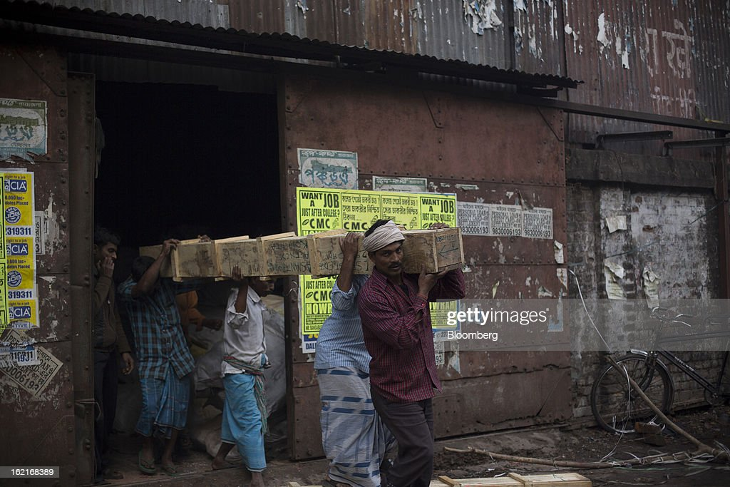 Laborers carry a wooden box out of a warehouse in Kolkata, India, on Tuesday, Feb. 19, 2013. India's slowest economic expansion in a decade is limiting profit growth at the biggest companies even as foreigners remain net buyers of the nation's stocks, according to Kotak Institutional Equities. Photographer: Brent Lewin/Bloomberg via Getty Images