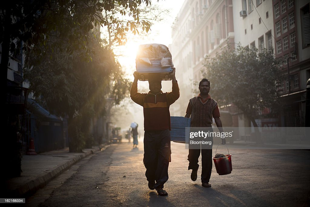 Laborers carry goods on the street in Kolkata, India, on Tuesday, Feb. 19, 2013. India's slowest economic expansion in a decade is limiting profit growth at the biggest companies even as foreigners remain net buyers of the nation's stocks, according to Kotak Institutional Equities. Photographer: Brent Lewin/Bloomberg via Getty Images
