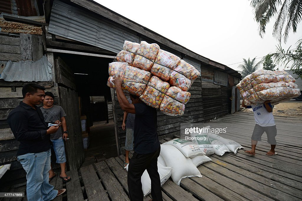 Laborers carry loads of goods into a shed near the Siak river in Pekanbaru, Riau Province, Indonesia on Friday, March 7, 2014. Indonesian central bank Governor Agus Martowardojo embarked on the country's most aggressive rate-increase cycle in eight years within a month of taking the helm in May to shore up the rupiah and damp price pressures. Photographer: Dimas Ardian/Bloomberg via Getty Images