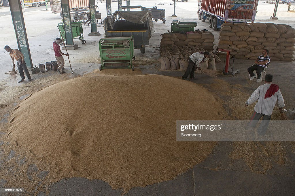 Laborers clean wheat at a grain market in the district of Jalandhar in Punjab, India, on Tuesday, April 16, 2013. Wheat harvest in India, the second-biggest grower, may reach a record for a sixth straight year after farmers increased use of high-yielding seeds and winter rains boosted crop prospects, a state-run researcher said. Photographer: Prashanth Vishwanathan/Bloomberg via Getty Images