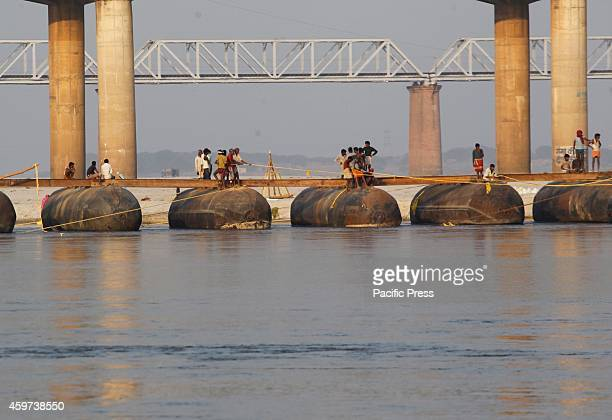 Laborers construct temporary pontoon bridge at the river Ganga before the annual 'Magh Mela' religious festival in Allahabad