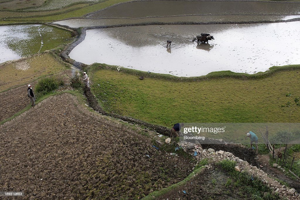 Laborers dig an irrigation ditch as farmers plough a paddy field and burn waste in fields near Ramban, India on Saturday, May 11, 2013. India's rupee fell to a six-month low and bonds dropped after the Federal Reserve flagged the possibility of trimming its debt purchases, raising concern inflows to higher-yielding emerging-market assets will slow. Photographer: Brent Lewin/Bloomberg via Getty Images