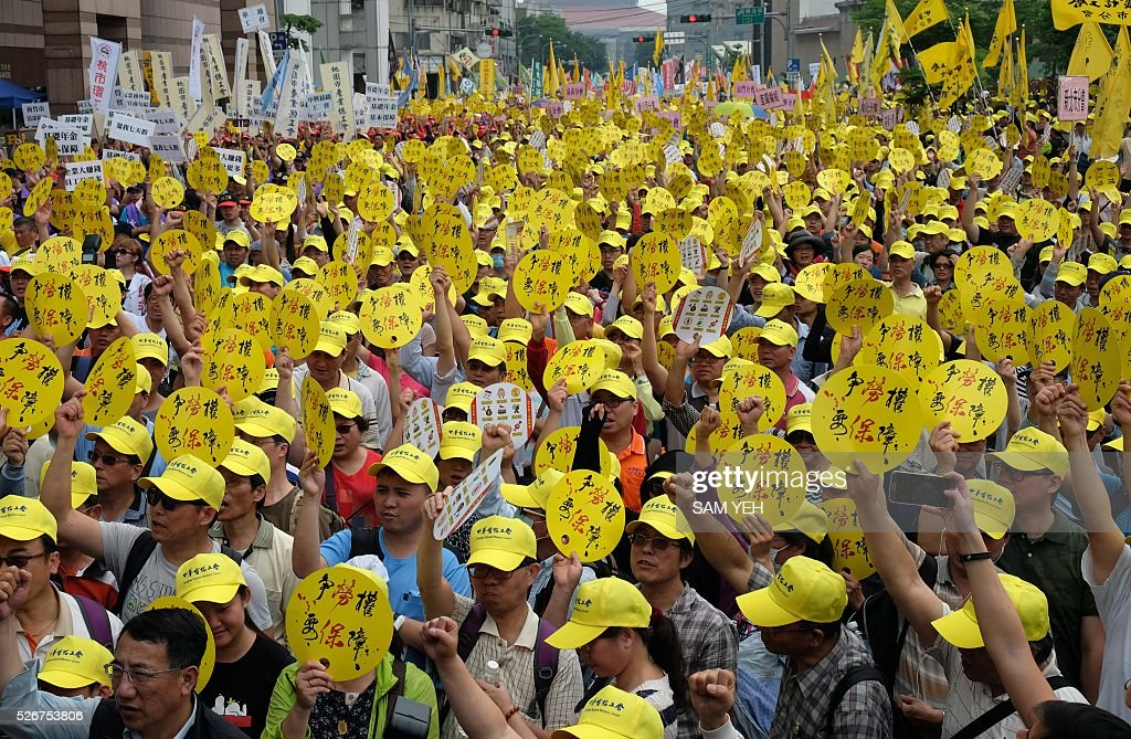 Laborers from different groups display signs that read 'fight for the labor's right, need the guarantee from the government' during a demonstration to mark the annual Labor's Day in Taipei on May 1, 2016. Thousands local labors and foreign workers march on the streets in Taipei to demand to protect their basic labor's rights. / AFP / SAM YEH